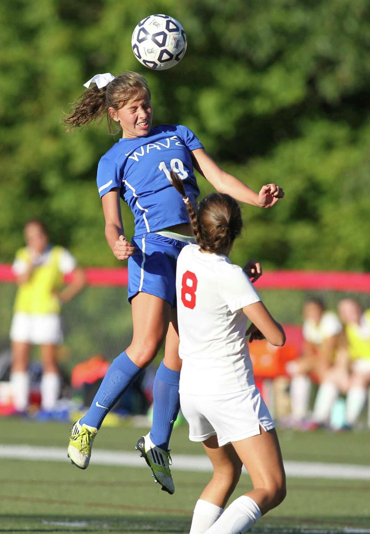 Darien's Morgan Sawitsky heads the ball over New Canaan's Mia Carroll during second half soccer action in New Canaan, Conn. on Monday Sept. 30, 2013. Darien won the match, 2-0.