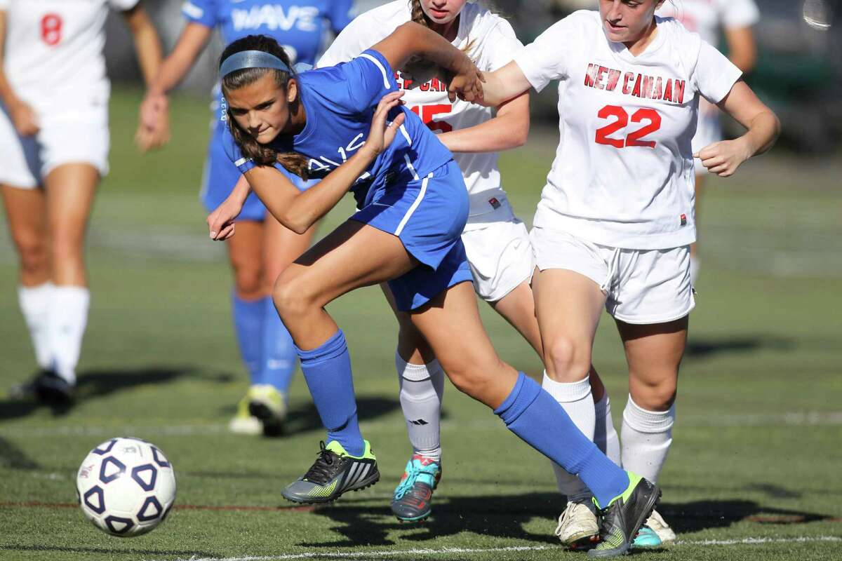 Darien soccer player Emma Lesko chases down a loose soccer ball despite the defensive efforts of New Canaan's Gabby Borea and Lizzy Burke. Darien would score a goal in each half to win the FCIAC game, 2-0, in New Canaan, Conn. on Monday Sept. 30, 2013.
