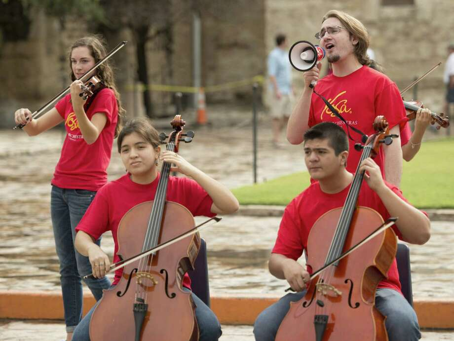 Cellist Joe Whitenton sings into a megaphone as fellow Youth Orchestras of San Antonio members, Jessie Atkins (from left), Mary Nerio and Federico Chávez-Torres, play during  Sícolovía on Sunday. Photo: Photos By Darren Abate / For The Express-News