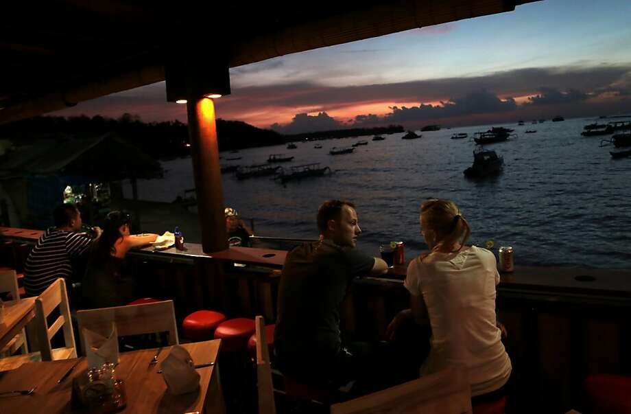 Happy hour in paradise: Tourists enjoy the sunset at a beach-side cafe in Nusa Lembongan, Bali. Photo: Dita Alangkara, Associated Press