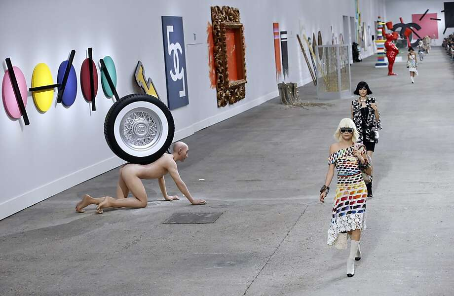 Oblivious to the naked man with the spare tire,British model Cara Delevingne presents a creation for Chanel during the 2014 Spring/Summer ready-to-wear collection fashion show at the Grand Palais in Paris. Photo: Patrick Kovarik, AFP/Getty Images