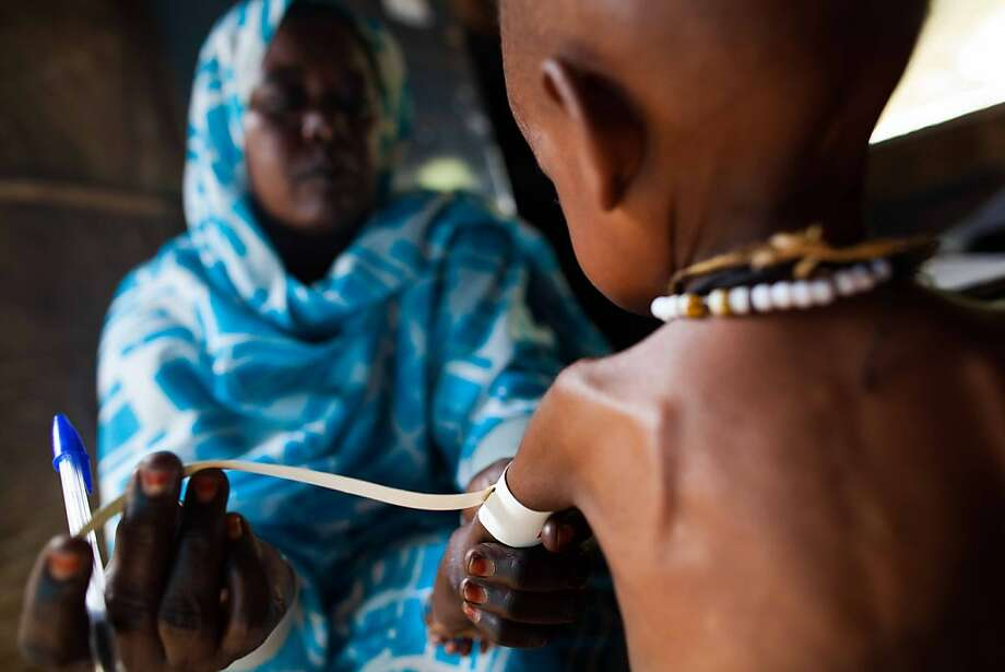 While the world laments Syria's plight, Darfur remains ignored: A nurse measures the arm of 