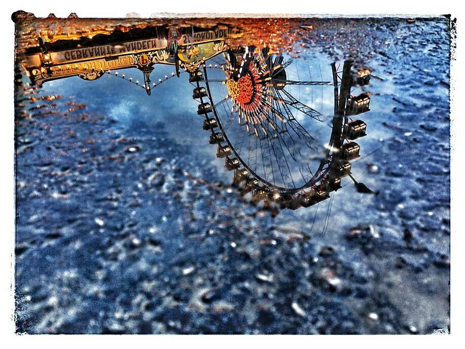 A Ferris wheel is reflected in a puddle during Oktoberfest at Theresienwiese in Munich. (Image created with digital filters.) Photo: Alexander Hassenstein, Getty Images