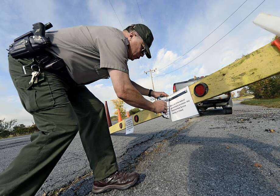 Park Ranger Keith Hatfield places a closing notice on a sawhorse at one of the entrances to Saratoga National Historical Park on Tuesday, Oct. 1, 2013, in Stillwater, N.Y. Photo: Skip Dickstein, Associated Press