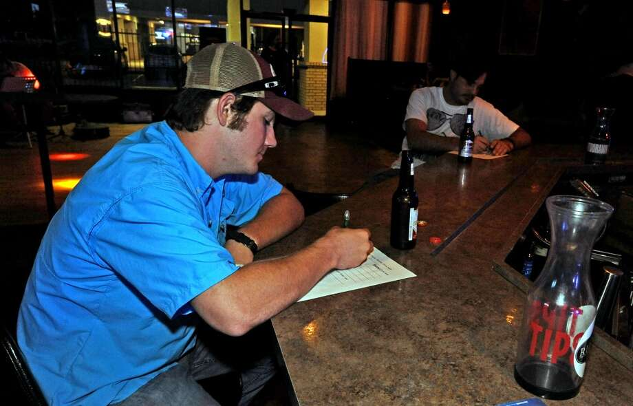 Cale Corbello puts pen to paper during the Thirty Thursday Trivia at the PaceSetter on Thurday, Augut 1, 2013. Photo taken: Randy Edwards/The Enterprise