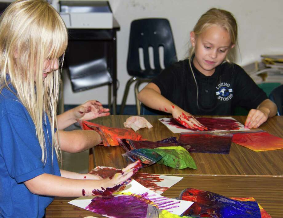 Mackenzie Pettigrew and Paige Huh finger-paint in Lona Dekenipp's second- and third-grade art class at Living Stones Christian School in Alvin. Photo: Carl Shier, Freelance / Freelance