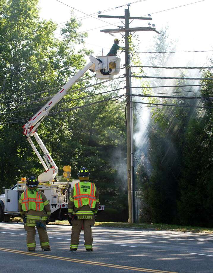 Firefighters wait as the electricity is turned off at the scene of an arcing wire on High Ridge Road and Cross Road in Stamford, Conn., on Tuesday, October 1, 2013. Photo: Lindsay Perry / Stamford Advocate