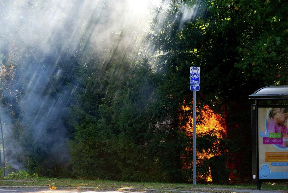 Firefighters put out a small fire at the scene of an arcing wire on High Ridge Road and Cross Road in Stamford, Conn., on Tuesday, October 1, 2013. Photo: Lindsay Perry / Stamford Advocate