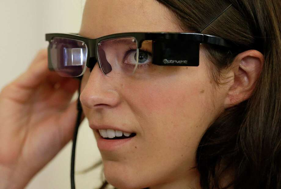Claire Collins is given a demonstration of Optinvent ORA-S augmented reality glasses at the GLAZED Conference, a conference for the business of wearable technology, in San Francisco, Monday, Sept. 30, 2013. The digital domain is creeping off our desktops and onto our bodies, from music players that match your tunes to your heart beat, to mood sweaters that change color depending on your emotional state _ blue for calm, red for angry. There are vacuum shoes that clean the floor while you walk and fitness bracelets, anklets and necklaces to track your calorie burning. (AP Photo/Jeff Chiu) ORG XMIT: CAJC101 Photo: Jeff Chiu / AP