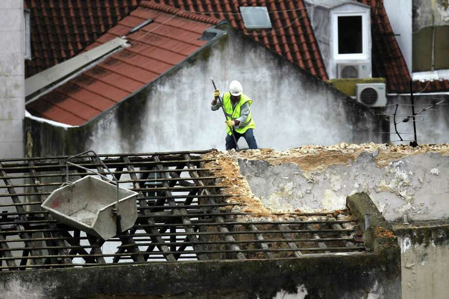 A constructions worker works on the roof of a building in Lisbon, Tuesday, Oct. 1, 2013. The eurozone's labor market appears to have stabilized, official figures indicated Tuesday, another sign that the eurozone economy is recovering from its longest-ever recession. Though Eurostat, the EU's statistics office, said the unemployment rate across the 17-member eurozone held steady at 12 percent in August, it found the number of people out of work fell for the third month running. That's the first time the region has enjoyed such a run since April 2011. (AP Photo/Francisco Seco) ORG XMIT: FS102 Photo: Francisco Seco / AP