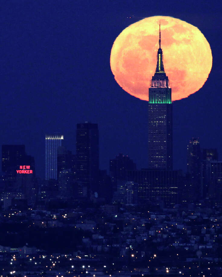 A full moon rises behind the Empire State Building in New York. Empire State Realty Trust, whose properties include the Empire State Building and buildings owned by Greenwich real estate magnates Anthony and Peter Malkin, raised $929.5 million in an initial public offering priced on Tuesday. Photo: Julio Cortez, Associated Press / Associated Press