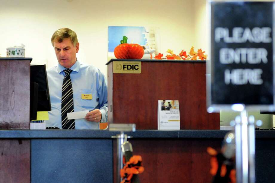 Bank teller Michael Celentano handles customer transactions on Tuesday, Oct. 1, 2013, at First Niagara Bank in Niskayuna N.Y. (Cindy Schultz / Times Union) Photo: Cindy Schultz / 00024065A
