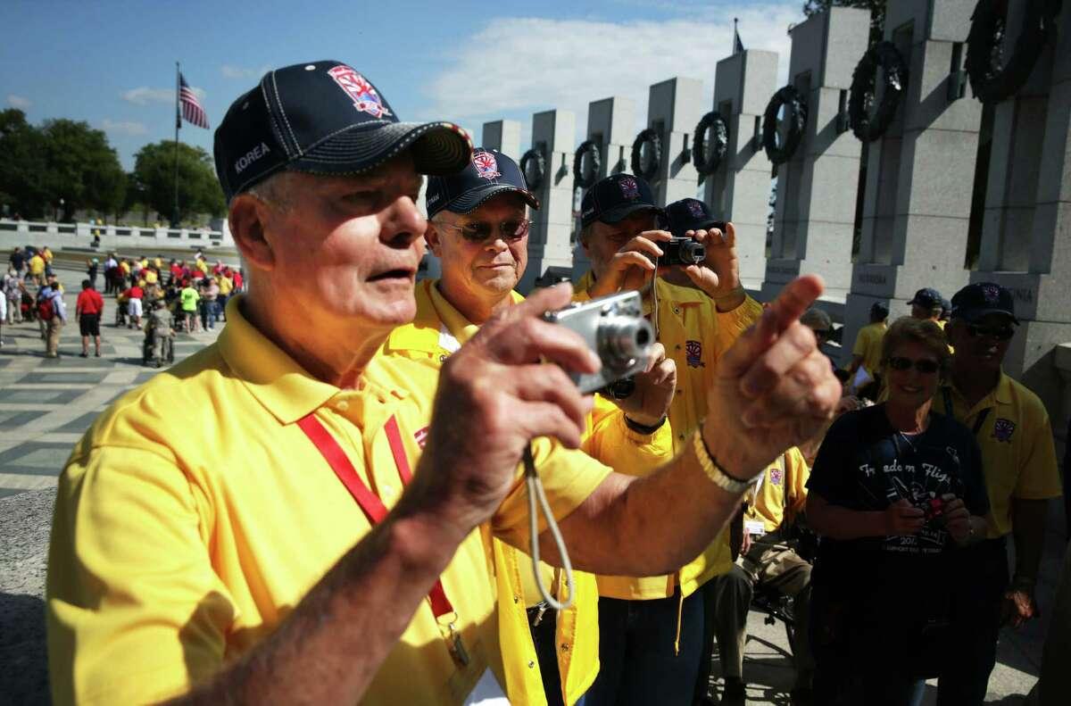 (L-R) Korean War veteran Bill Bakley, Vietnam War veterans Norman Tjelmeland, and Stanley Twedt, of Ames, Iowa, snap pictures at the World War II Memorial after they were let in during a government shutdown October 1, 2013 in Washington, DC.