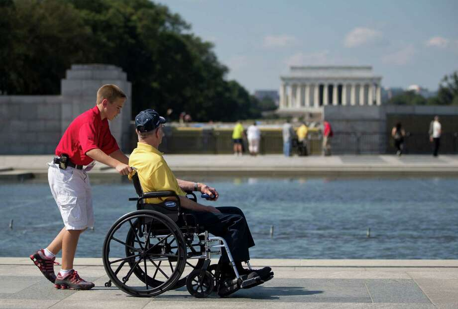 Korean War veteran Robert Olson, from Iowa, is pushed in his wheelchair by Zach Twedt, also from Iowa, around the National World War II Memorial in Washington, Tuesday, Oct. 1, 2013. Photo: Carolyn Kaster, Associated Press / AP