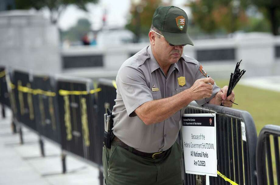 US Park Ranger Richard Trott places a closed sign on a barricade in front of the World War II monument in Washington, DC, October 1, 2013. Photo: JIM WATSON, AFP/Getty Images / AFP