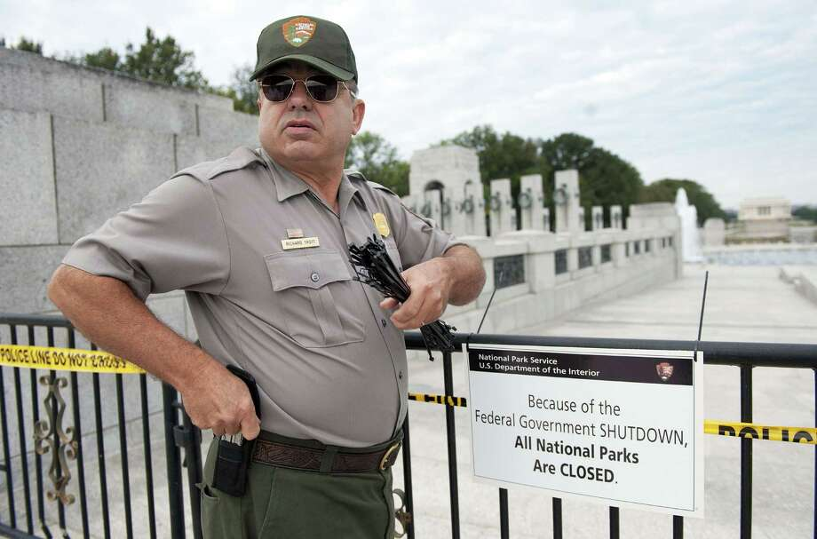 US Park Ranger Richard Trott places a closed sign on a barricade in front of the World War II Memorial monument in Washington, DC, October 1, 2013.  The US government shut down Tuesday for the first time in 17 years after a gridlocked Congress failed to reach a federal budget deal amid bitter brinkmanship. Some 800,000 federal workers have been furloughed in a move reminiscent of two previous shutdowns -- for six days in November 1995 and 21 days from December that year into early 1996. Photo: JIM WATSON, AFP/Getty Images / AFP