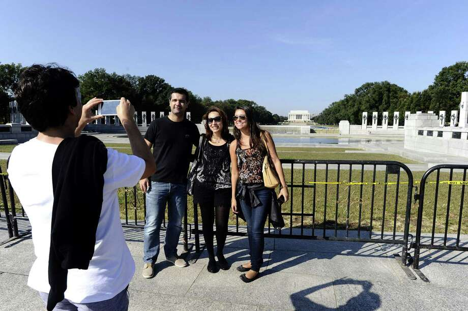 Tourists have their picture taken near barriers at the World War II Memorial  monument in Washington, DC, on October 1, 2013. The US government shut down Tuesday for the first time in 17 years after a gridlocked Congress failed to reach a federal budget deal amid bitter brinkmanship. Some 800,000 federal workers have been furloughed in a move reminiscent of two previous shutdowns -- for six days in November 1995 and 21 days from December that year into early 1996. Photo: JEWEL SAMAD, AFP/Getty Images / AFP