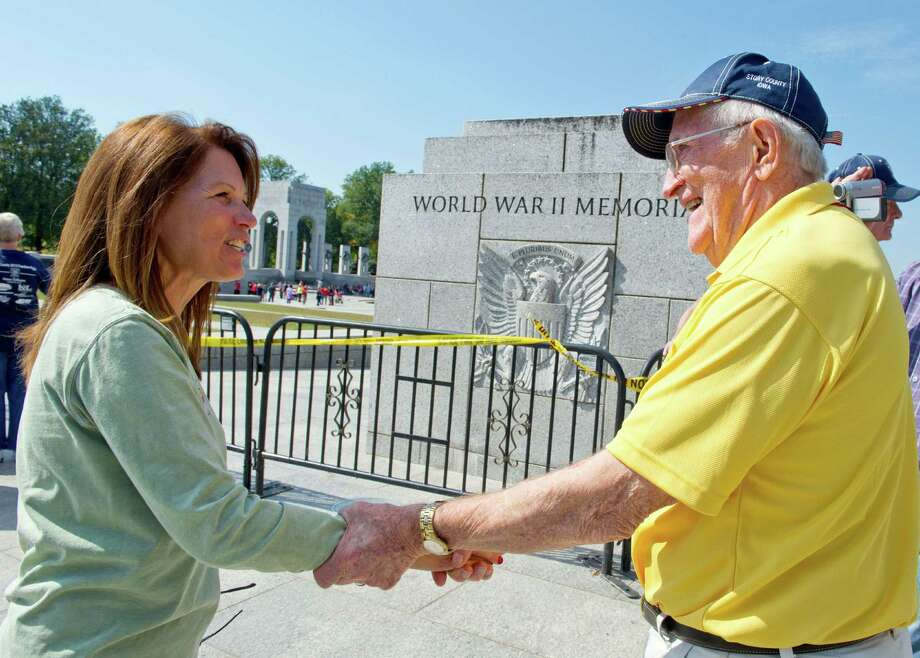 US Rep. Michelle Bachmann(L),R-MN, greets a US military war veteran as he arrives to visit the World War II Memorial on the National Mall in Washington, DC, on October 1, 2013. The US Park Service opened the area to the veterans who are brought to Washington to visit and reflect at their memorials. Top  through the efforts of Honor Flight,  a non-profit organization created solely to honor America's veterans for all their sacrifices. The US government shut down Tuesday for the first time in 17 years after a gridlocked Congress failed to reach a federal budget deal amid bitter brinkmanship. Some 800,000 federal workers have been furloughed in a move reminiscent of two previous shutdowns -- for six days in November 1995 and 21 days from December that year into early 1996. Photo: KAREN BLEIER, AFP/Getty Images / AFP