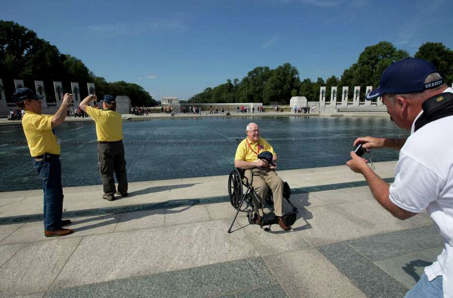 Korean War veteran Frederick Jenkins, from Iowa, third from left, poses for a photograph at National World War II Memorial in Washington, Tuesday, Oct. 1, 2013. Veterans who had traveled from across the country were allowed to visit the National World War II Memorial after it had been officially closed because of the partial government shutdown. After their visit, the National World War II Memorial was closed again. Photo: Carolyn Kaster, Associated Press / AP