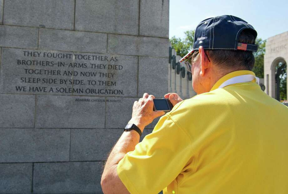 A US military war veteran takes photos at the World War II Memorial on the National Mall in Washington, DC, on October 1, 2013. Photo: KAREN BLEIER, AFP/Getty Images / AFP