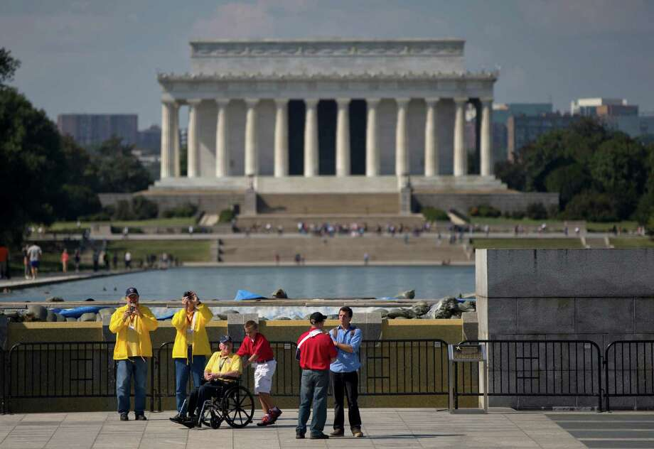 Robert Olson, a Korean War veteran from Iowa, third from left, is pushed in his wheelchair by Zach Twedt, also from Iowa, fourth from left around the National World War II Memorial, Tuesday, Oct. 1, 2013 in Washington. Photo: Carolyn Kaster, Associated Press / AP