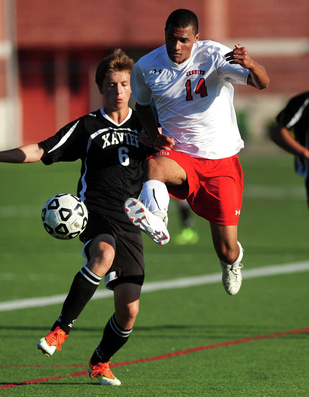 Fairfield Prep's Matt Crowe leaps in front of Xavier's Jason Hoops to intercept the ball, during boys high school soccer action in Fairfield, Conn. on Tuesday October 1, 2013.