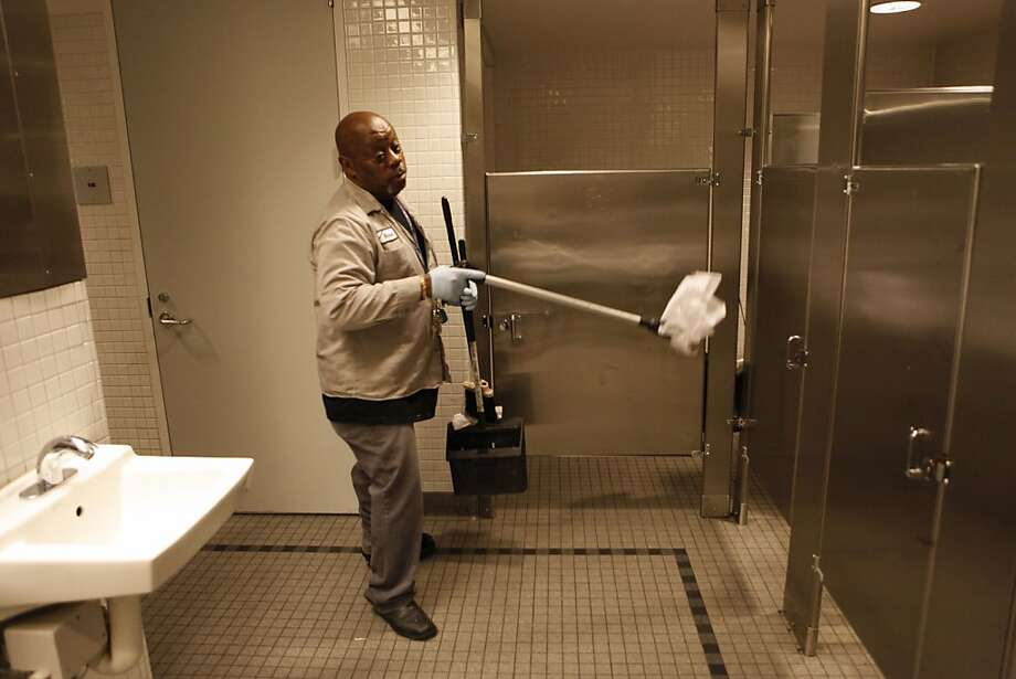 Custodian Richard Mathews clears debris from a San Francisco Public Library main branch bathroom, which is frequently trashed by transients and others. Photo: Michael Macor, The Chronicle