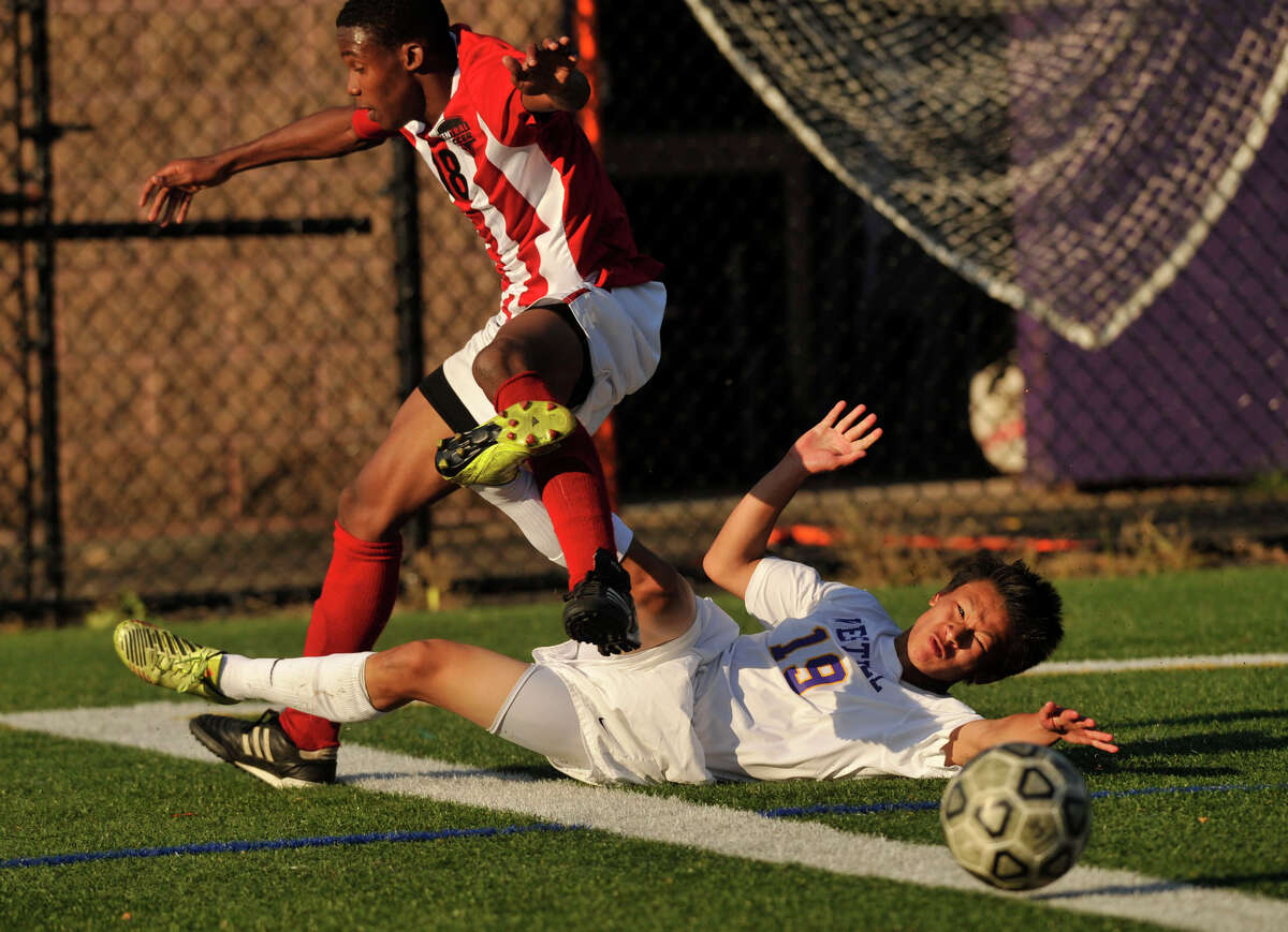 Westhill's Charles Teeters makes a slide tackle to take the ball from Central's Ricardo Jean-Pierre during their game at Westhill High School in Stamford, Conn., on Tuesday, Oct. 1, 2013. Westhill beat Central, 2-0.