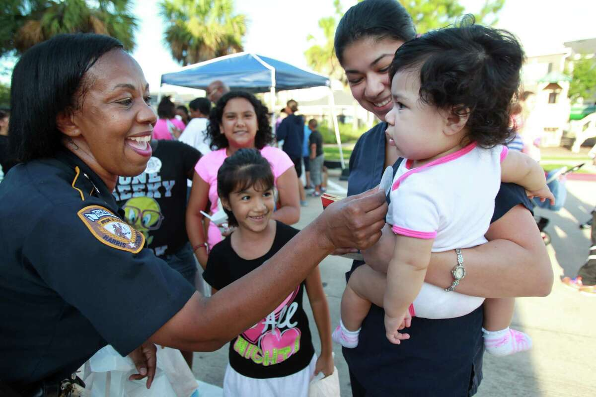 Harris County Sheriff's Deputy C.C. Parker meets residents Gabriela Pena, 6, and Lidia Pena, carrying daughter Lilia Pena, 7 months, during the National Night Out gathering at the Millstone Apartment Complex on Tuesday, Oct. 1, 2013, in Katy.