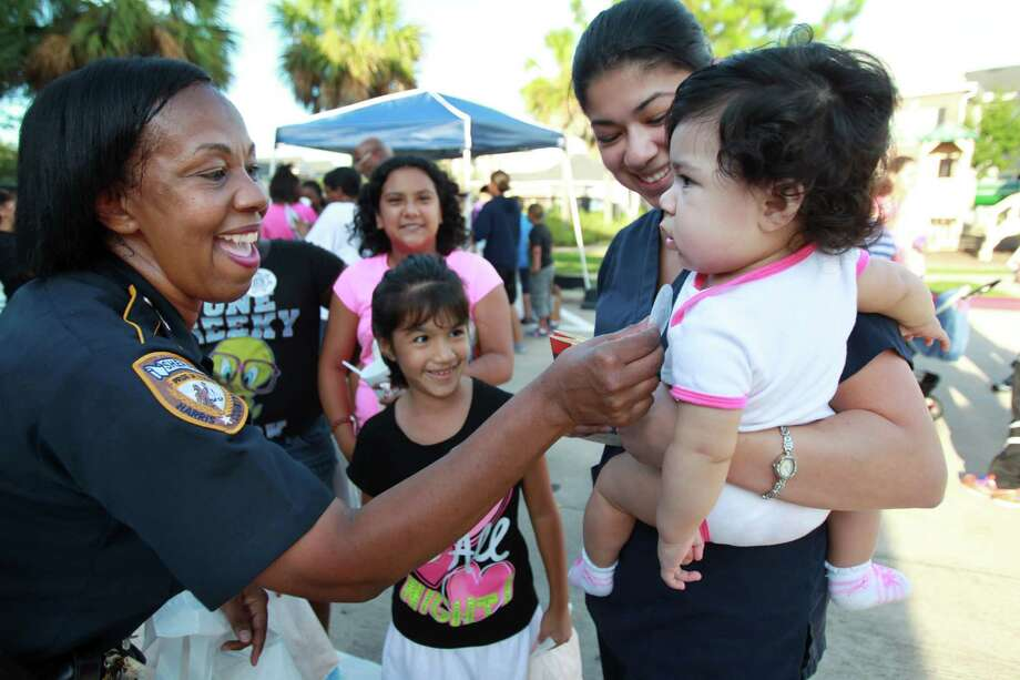 Harris County Sheriff's Deputy C.C. Parker meets residents Gabriela Pena, 6, and Lidia Pena, carrying daughter Lilia Pena, 7 months, during the National Night Out gathering at the Millstone Apartment Complex on Tuesday, Oct. 1, 2013, in Katy. Photo: Mayra Beltran, Houston Chronicle / © 2013 Houston Chronicle