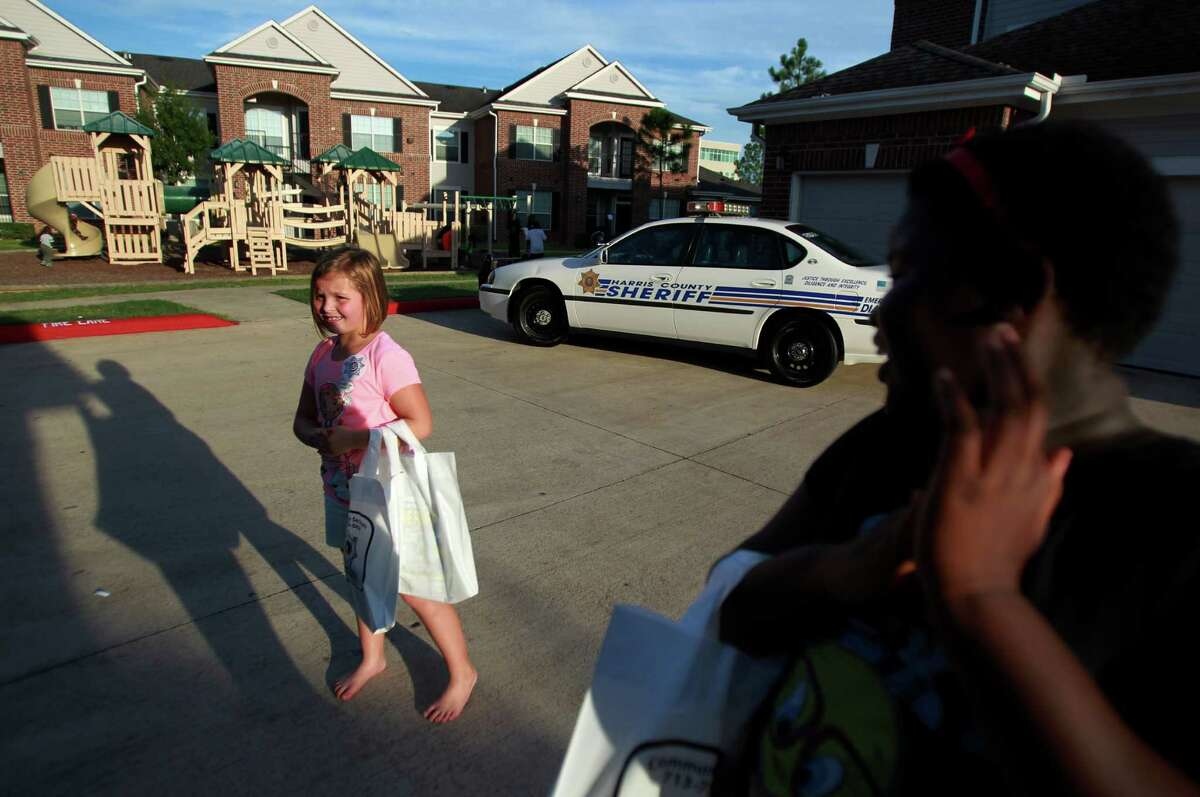 Ava Peters, 7, and her friend N'namarie Kebe, 9, enjoy snacks and free gifts from HCSO during the National Night Out gathering at the Millstone Apartment Complex on Tuesday, Oct. 1, 2013, in Katy.
