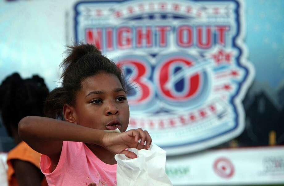 Tamyra Hall, 8, eats popcorn during the National Night Out gathering at the Millstone Apartment Complex on Tuesday, Oct. 1, 2013, in Katy. Photo: Mayra Beltran, Houston Chronicle / © 2013 Houston Chronicle