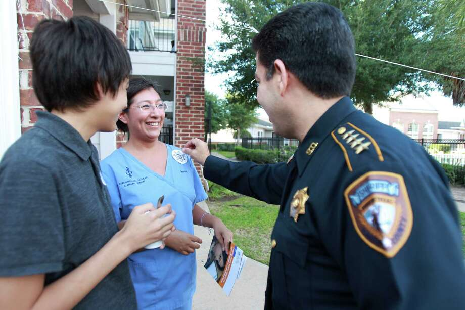 Adrian Medina laughs with her mother Nancy Medina as Harris County Sheriff Adrian Garcia puts a deputy badge sticker on them. Photo: Mayra Beltran, Houston Chronicle / © 2013 Houston Chronicle