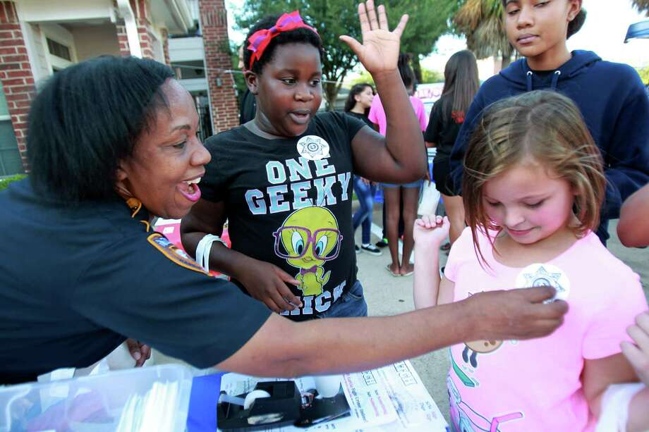 "HCS Deputy C.C. Parker pins a deputy sticker badge on Ava Peters, 7, as friend N'namarie Kebe, 9, says ""You are an officer now"" during the National Night Out gathering at the Millstone Apartment Complex on Tuesday, Oct. 1, 2013, in Katy. Photo: Mayra Beltran, Houston Chronicle / © 2013 Houston Chronicle"