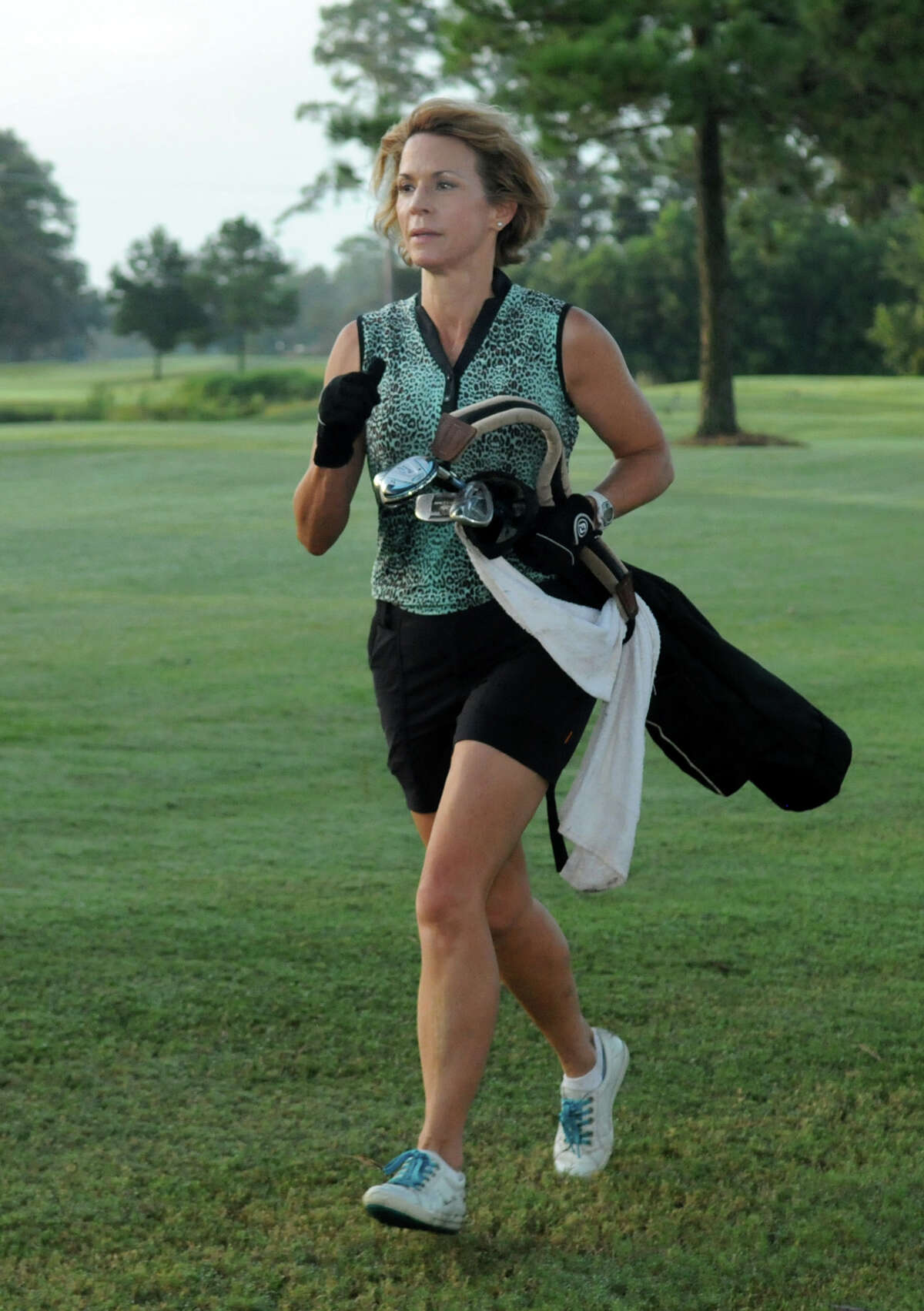 In Speedgolf, Herb Lipsman, general manager of Redstone Golf Club, uses the hands-on approach to carrying fewer clubs, while Redstone director of golf fitness Pam Owens, below, opts for a smaller golf bag.