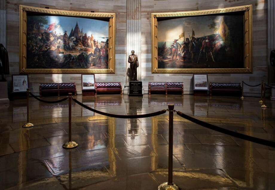 Normally filled with visitors and tourists, the empty Rotunda at the U.S. Capitol is seen in Washington, Tuesday, Oct. 1, 2013, after officials suspended all organized tours of the Capitol and the Capitol Visitors Center as part of the government shutdown. A statue of President Gerald R. Ford at center is illuminated amid large paintings illustrating the history of the United States. (AP Photo/J. Scott Applewhite) ORG XMIT: DCSA124 Photo: J. Scott Applewhite / AP