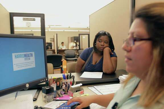 Vanessa Danielle Cotton left, is helped with enrollment in the Affordable Care Act at the Harris Health System eligibility center with ACA Certified Application Counselor Lillian Ardon Tuesday, Oct. 1, 2013, in Houston.