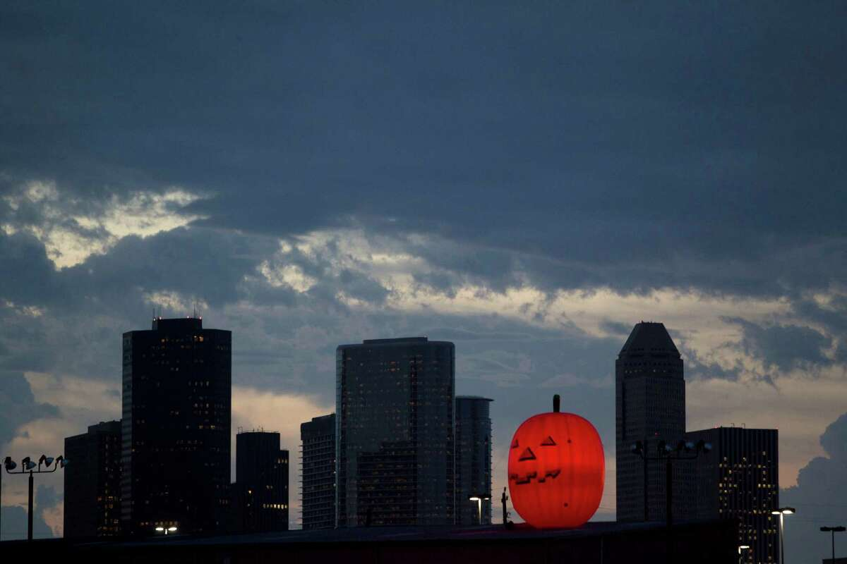 An inflatable pumpkin on top of the Party Boy party goods store along I-10 at Studemont ushers in October near downtown Tuesday, Oct. 1, 2013, in Houston.