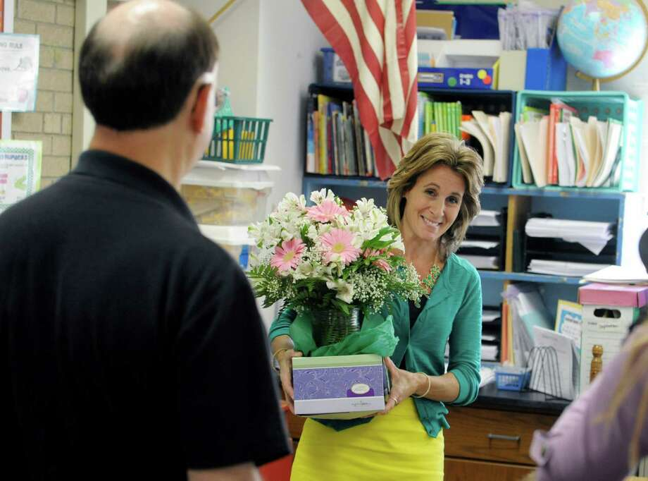 Woodlawn Elementary School third grade teacher,  Christina Miskovsky holds flowers given to her by Office Max employees during a surprise event to award her the Office Max A Day Made Better award on Tuesday, Oct. 1, 2013, in Schenectady, NY.  Each year, OfficeMax and its nonprofit partner AdoptAClassroom.com, work with school principals nationwide to select and recognize 1,000 deserving teachers.  The recipient receives $1,000 worth of school supplies.  Miskovsky's award was through the Rotterdam Office Max.   (Paul Buckowski / Times Union) Photo: Paul Buckowski / 00024059A