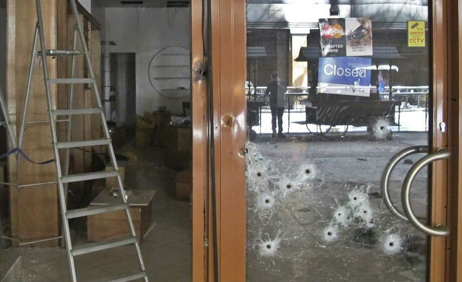 Bullet holes pepper the door of a shop in the Westgate mall. Kenya's security chiefs are being criticized for a messy rescue response. Photo: Rukmini Callimachi / Associated Press