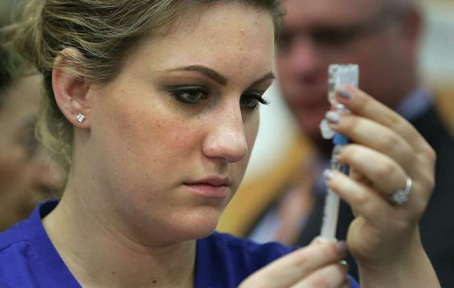 Registered nurse Shauna Kohleffel prepares a flu shot at Harris Middle School as part of Texas' first Influenza Awareness Day. Public health officials also were on hand, to educate students about the flu. Photo: Photos By Bob Owen / San Antonio Express-News