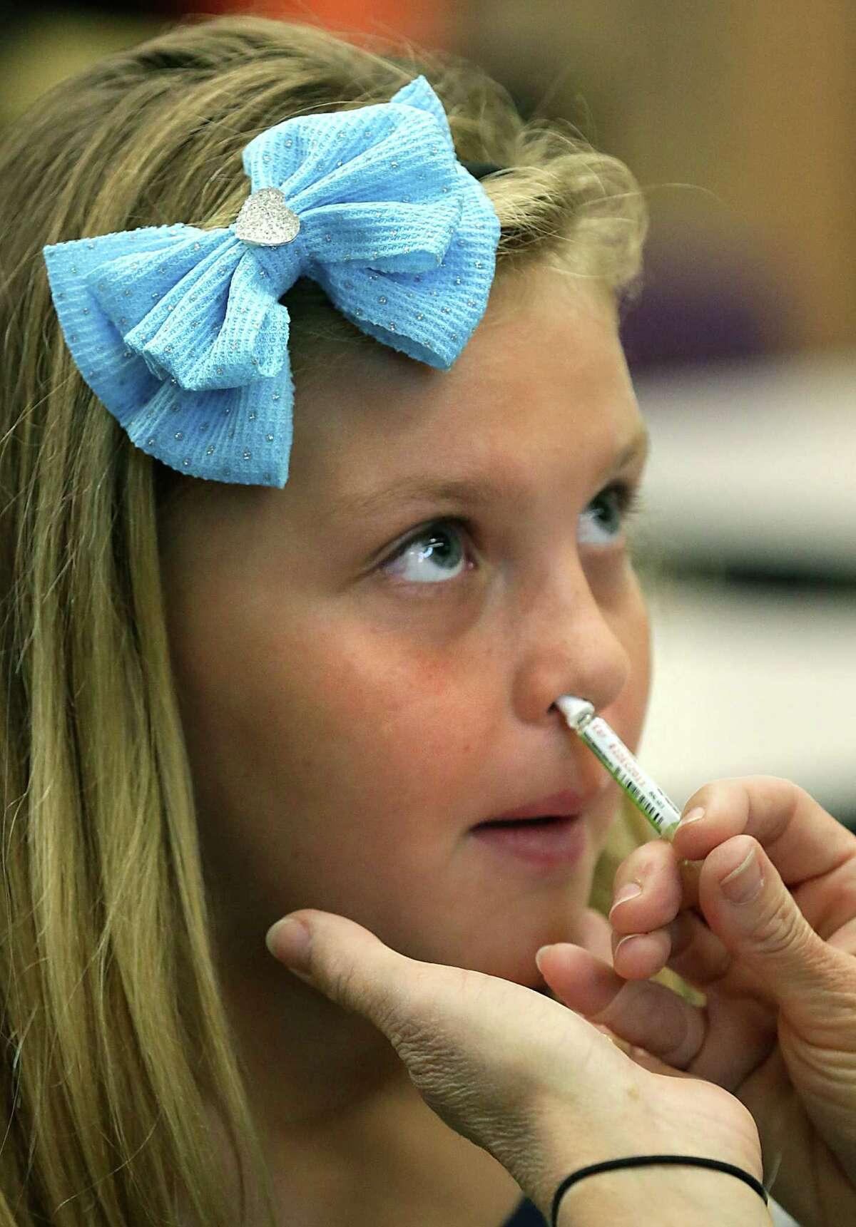 Fourth-grader Breanna Murphy of Northern Hills Elementary School receives the inhaled flu vaccine.
