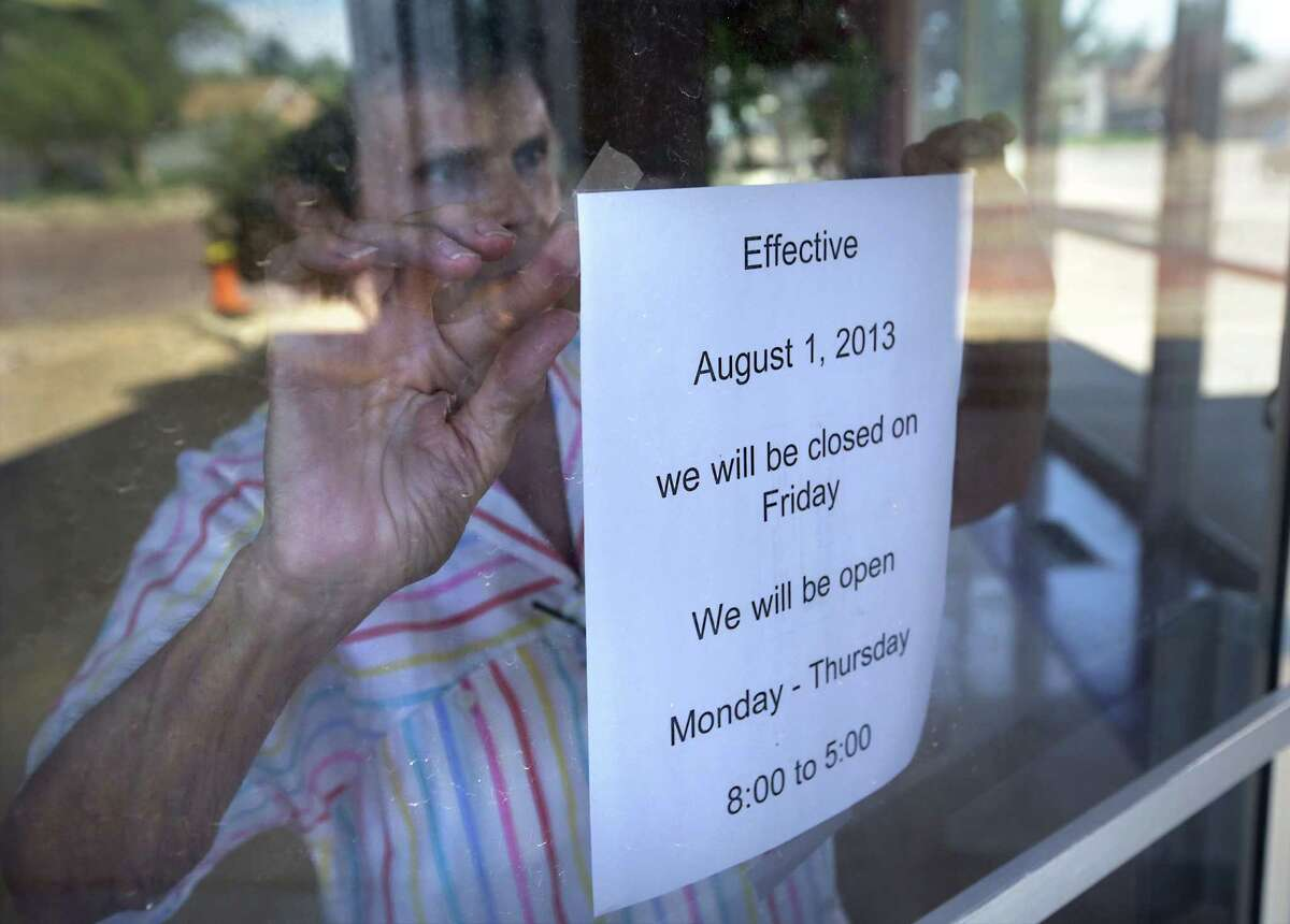 Glenda Lancaster, co-owner of Eaton Craig Stationery and Printing Co. in Plainview, posts a sign advising customers the store no longer will be open on Fridays. The company lost half its business when its biggest client, Cargill Beef, closed.