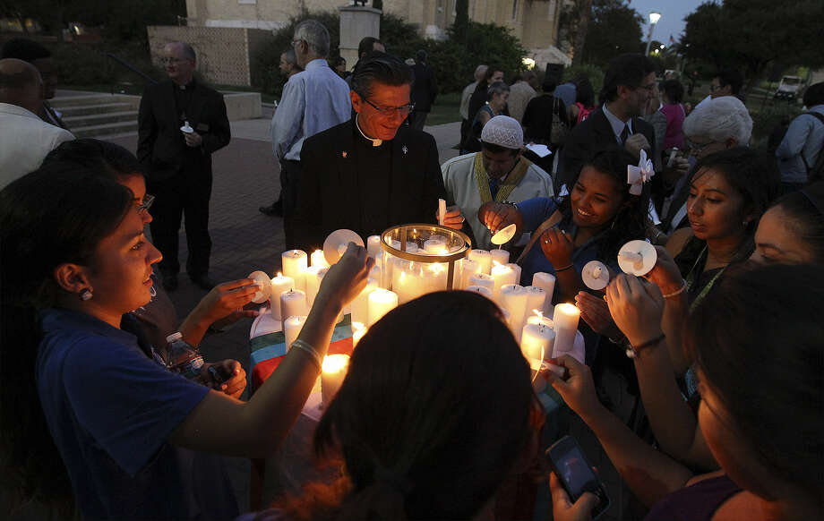 Archbishop Gustavo García-Siller (top) joins others in lighting candles at the closing vigil at St. Mary's University for the International Prayer for Peace on Tuesday. Photo: Photos By Kin Man Hui / San Antonio Express-News