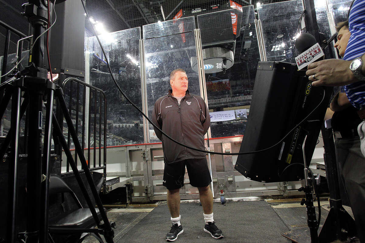 Coach Peter Horachek talks on camera with the ice rink in the background as the Rampage hockey team conducts media day at the AT&T Center on October 1, 2013
