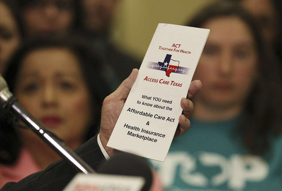 Bexar County Judge Nelson Wolff holds a pamphlet aimed at providing residents with information about the new health care program. Photo: Kin Man Hui / San Antonio Express-News
