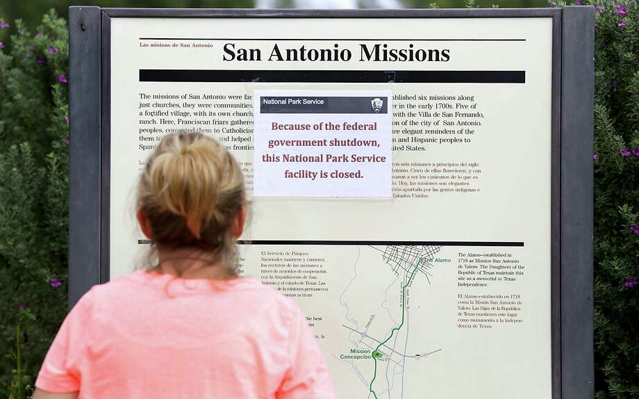 Cathy Tappon of Wisconsin stops to read the sign at Mission San José stating the national park is closed, due to the government shutdown.