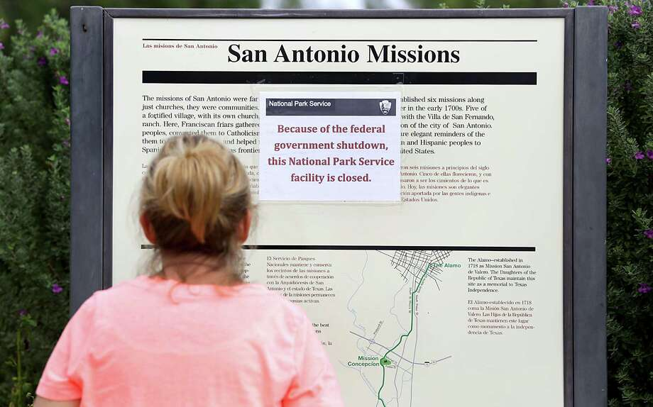 Cathy Tappon of Wisconsin, stops to read the sign at Mission San Jose stating the National Park is closed due to the government shutdown, Oct. 1, 2013. Photo: BOB OWEN, San Antonio Express-News / © 2012 San Antonio Express-News