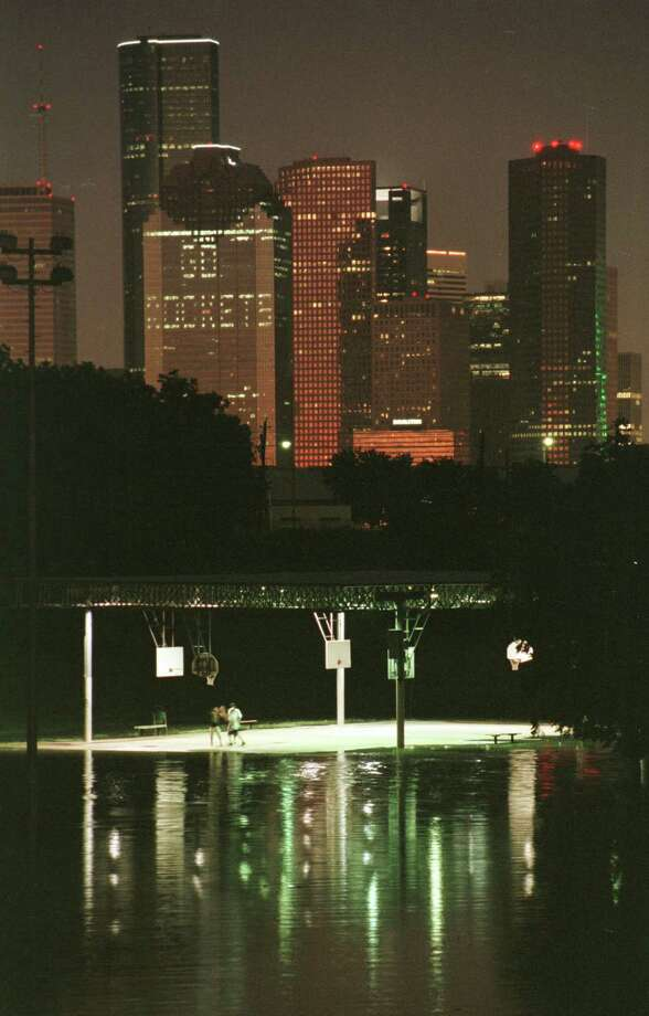 The Stude park basketball court seems to float in bayou floodwaters as a pick-up game is underway with the 'Go Rockets' sign lit in the downtown Heritage Plaza building on May 24, 1997. (Richard Carson photo) Photo: Richard Carson, Houston Chronicle / Houston Chronicle