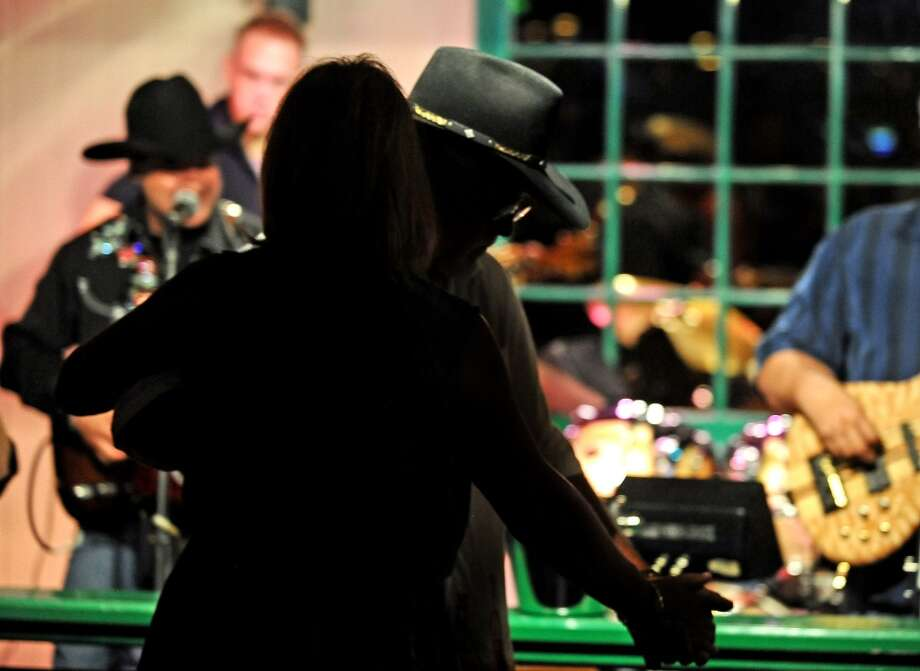 B.B. & Company take the stage at MacKenzie's Pub on Thursday as they have for the past 13 years. Giving the crowd enough time to grab a sip of their drink between each song, B.B. & Company keeps the dance floor packed with their country music covers and originals.  Photo taken Thursday, August 8, 2013. Photo taken: Randy Edwards/The Enterprise Photo: Beaumont Enterprise